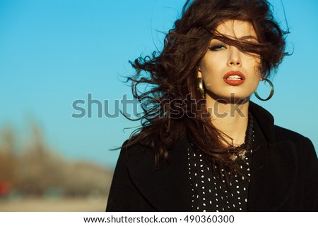 Spring, autumn high fashion concept. Gorgeous young girl with long dark glossy hair in black cocktail dress, coat on the beach. Hollywood star, diva style. Close up. Copy-space. Outdoor shot