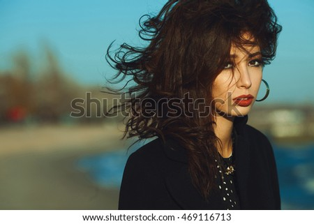 Spring, autumn high fashion concept. Gorgeous young girl with long dark glossy hair in black dress and coat on the beach. Hollywood star, diva style. Close up. Copy-space. Outdoor shot