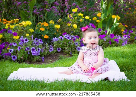 Spring Baby Girl wearing a pink summer dress on a blanket over green grass. - stock photo