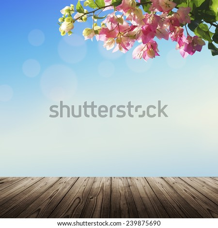 Spring background with wooden deck (table) blue sky and blooming flowers - stock photo