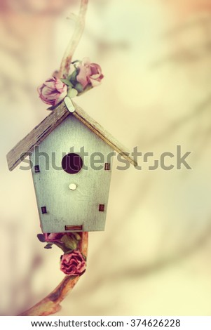 Spring background.Wooden feeder at the decorative tree. - stock photo