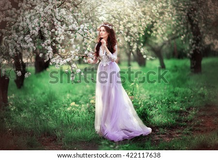 Spring Beautiful romantic brunette girl standing in blooming apple garden .Dreaming princess in lilac beautiful lace dress and wreath looking afar and dreaming. Fairy tale and art work.Warm colors