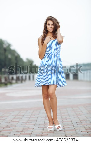 Spring beautiful woman in summer dress walking in city river park enjoying weekend. Playful and beautiful caucasian girl on warm sunny day.