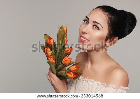 Spring beauty model studio shooting. Portrait of smiling young beautiful woman  with flowers orange tulips on white background. Fashion fresh natural makeup. Tenderness. Romantic style. Enjoy life. - stock photo