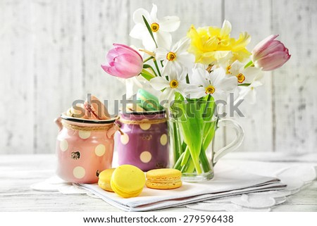 Spring bouquet in glass mug  and tasty macaroons on color wooden background - stock photo