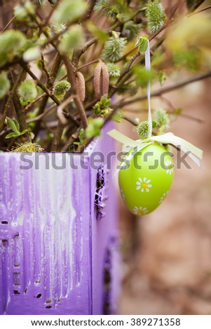 Spring bouquet of blossoming willow in lilac vase. Easter decoration  in the garden. - stock photo