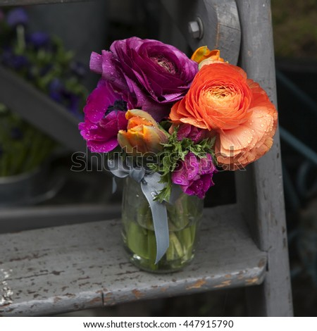 Spring bouquet with purple  ranunculus, orange tulips and anemones in a glass jar on the stairs - stock photo