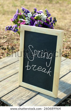 Spring break concept. Beautiful wild flowers in vase and frame on wooden table outdoors - stock photo