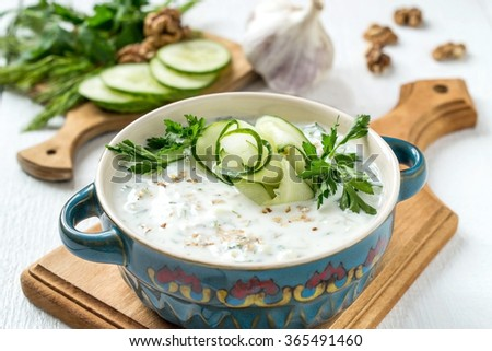 Spring bulgarian cold soup tarator with yogurt, ingredients: cucumber, garlic, dill, walnuts on a white wooden table. Selective focus - stock photo
