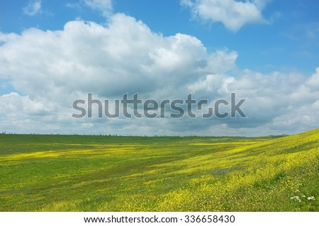 Spring cloudy landscape with yellow wild flowers field. Hills valley in Crimea - stock photo