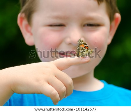 Spring concept with close up of a painted lady butterfly, Vanessa cardui, being held by child playing outdoors in nature