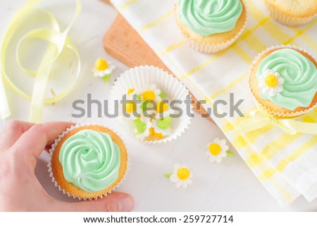 Spring cupcakes preparation - hand holding cupcake, sugar flowers, ribbon, plaid napkin, white wood background, top view - stock photo