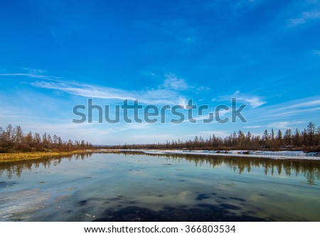 Spring day landscape with river, ice, taiga and cloudy sky