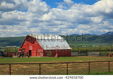 Spring day with a red barn in rural Wyoming, USA. - stock photo