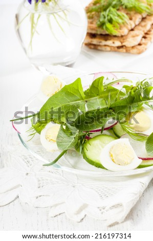Spring diet salad with eggs, radish, cucumbers and dandelion leaves