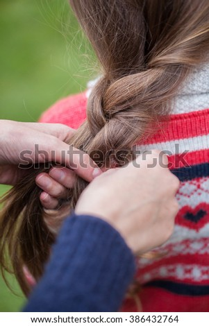 Spring fairy. Portrait of beautiful little girl with brownish blond hair standing outdoor. Sister makes her pigtails. - stock photo