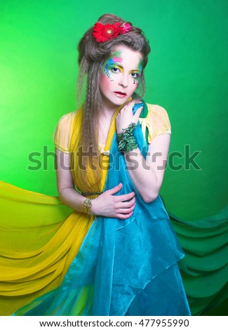 Spring fairy. Young woman in creative image posing with bright fabric's and flowers.