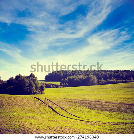 Spring Farm Landscape with Plowed Field on the Background of Beautiful Clouds and Blue Sky. Ploughed Soil. Agriculture Concept. Copy Space. Instagram Styled Toned Photo. - stock photo