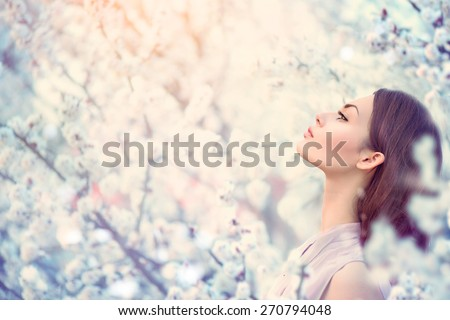 Spring fashion girl outdoor portrait in blooming trees. Beauty Romantic woman in flowers. Sensual Lady. Beautiful Woman Enjoying Nature. Romantic beauty in fantasy orchard - stock photo