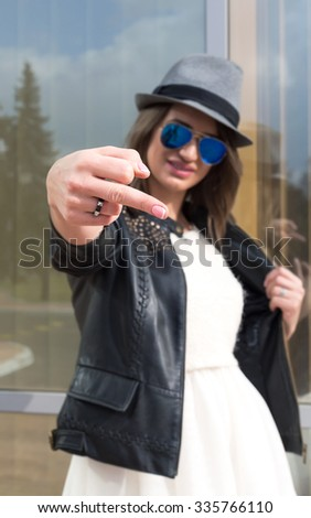 Spring fashion image of young woman wearing white dress,black leather coat and grey hat.Rebellious girl in a hat shows a middle finger. - stock photo