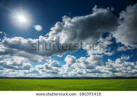 spring field and cloudy sky - stock photo