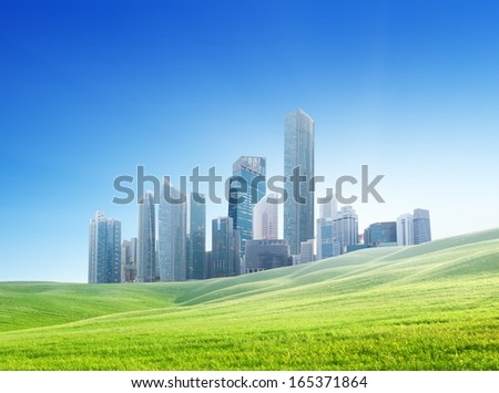 spring field and modern city  - stock photo