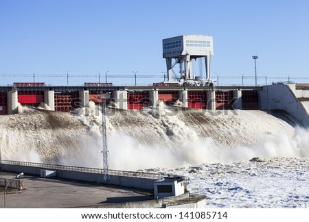 Spring flood water flowing on hydroelectric power station dam  - stock photo