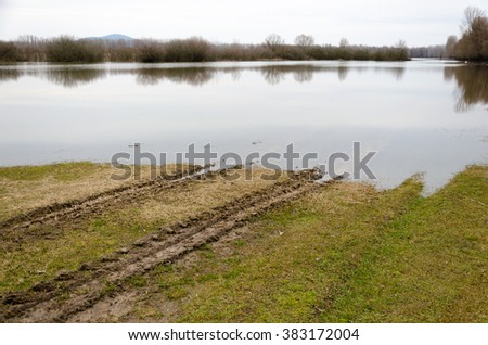 Spring flooding. Natural disaster. Flooding of the Tisza (Tisa)  river at Tiszalok, Hungary. Rut on the wet field, - stock photo