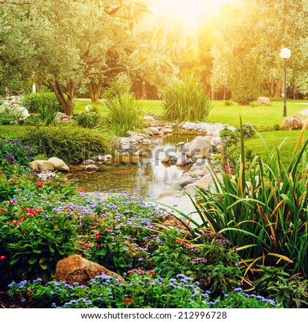 Spring flowers against sun in the Asian garden with a pond with lens flare, instagram effect - stock photo
