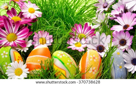 Spring flowers and happy colorful Easter eggs on fresh grass - stock photo