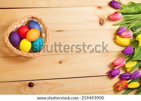 Spring Flowers bunch and easter eggs at wood floor texture. Beautiful Tulips bouquet gift. Easter  background. Springtime or summertime. Invitation card design with space for your text - stock photo