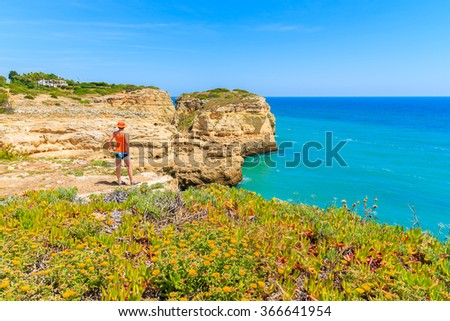 Spring flowers in foreground with young woman tourist standing on cliff rock and looking at sea, Portugal