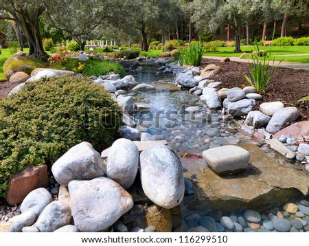 Spring flowers in the Asian Japanese garden with a pond and olive trees - stock photo