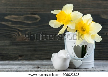 Spring flowers in vase on wooden table. Spring, easter or gardening concept - stock photo