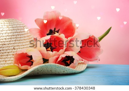 Spring flowers tulips with a straw sun hat