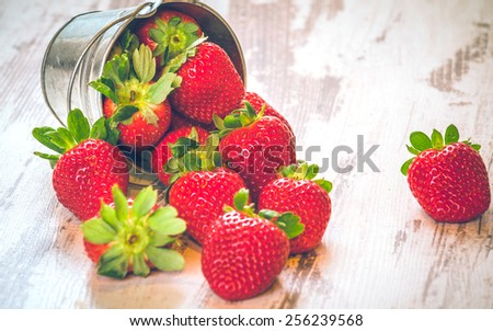 Spring fruits, strawberries in an aluminum bucket on a vintage wooden table. - stock photo