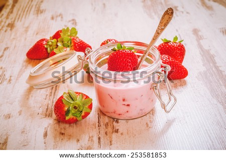 Spring fruits, strawberries with strawberry yogurt on a vintage wooden table.