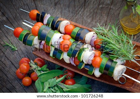 Spring garden barbecue. Vegetable kebabs with cherry tomatoes, zucchini, eggplant on wooden background - stock photo