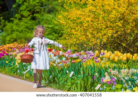 Spring garden, spring flowers, adorable little girl and tulips - stock photo