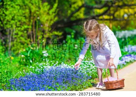 Spring garden, spring flowers, dorable little girl and cornflowers - stock photo