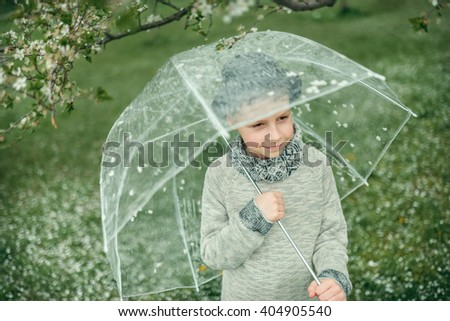 Spring garden with flowering trees a cute little boy with a hat under a transparent umbrella - stock photo