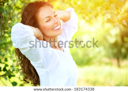 Spring Girl enjoying nature. Beautiful Young Woman Outdoors. Healthy Smiling Girl in the Green Park. Sunny day  - stock photo