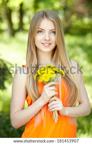 Spring girl. Lovely blond girl with bunch of dandelions outdoors looking up