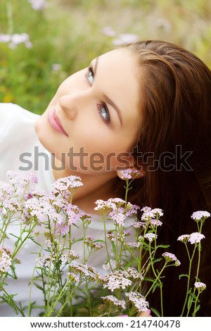 Spring girl lying on the field at summer time  - stock photo