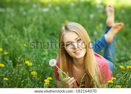 Spring girl lying on the field of dandelions