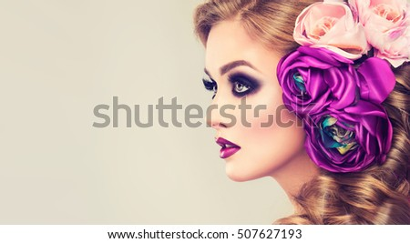 Spring  girl with trendy make up  smoky eyes .  Hairstyle curly ponytail with violet   artificial rose flowers on the head.
