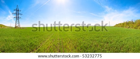 Spring green cereals field morning panorama, blue sky with sunshine patch and plane traces (high-voltage line). Seven shots stitch image. - stock photo
