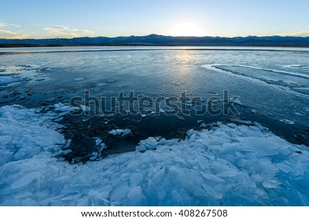 Spring Icy Lake - Sunset view of a melting ice mountain lake. - stock photo