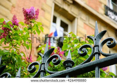 Spring in Paris. Blossoming lilac flowers and typical Parisian building with French flag hanging out from the window. Selective focus on the forging fence. - stock photo