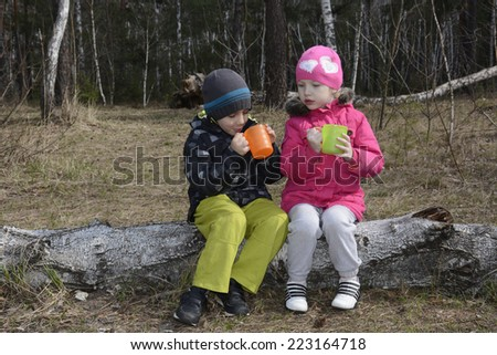Spring in the pine forest sitting on a log and two small children drink tea from colored cups. - stock photo